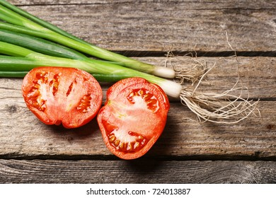 Spring onions and tomatoes on the vintage wooden table