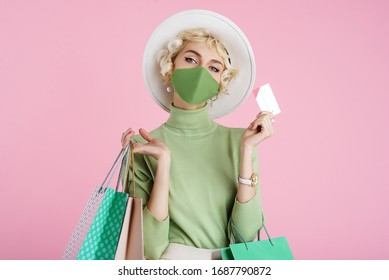 Spring online shopping during quarantine conception: fashionable woman wearing protective mask posing with colorful paper bags and plastic bank card. Pink background. Copy, empty space for text
