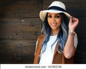 Spring outfit - Beautiful African Italian woman with granny hairstyle,  white t-shirt, tight white pants, white hat and high heeled sandals, and brown sleeveless.