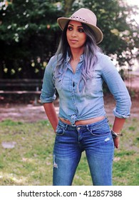 Spring outfit - Beautiful smiling tattoed african italian girl with granny hairstyle, wearing jeans shirt, ripped denim pants, camel heels, wide-brimmed hat (country style).