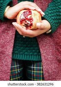 Spring outfit - Pomegranate in the hands of a young woman, who dresses marsala red sleeveless, sweater and tartan trousers