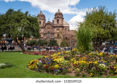Spring photo at Cuzco main square called Plaza de Armas where you can see a beautiful cathedral behind and many colorful flowers at the front. Cusco, Peru. September 15, 2018