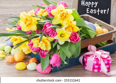 spring pink  tulips and yellow daffodil flowers with easter eggs and gift box