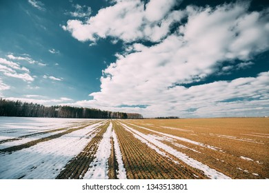 Spring Plowed Field Partly Covered Winter Melting Snow Ready For New Season. Ploughed Field In Early Spring. Farm, Agricultural Landscape Under Scenic Cloudy Sky.