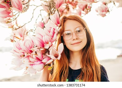 Spring portrait of adorable red-haired preteen kid girl with magnolia flowers, child wearing eyeglasses