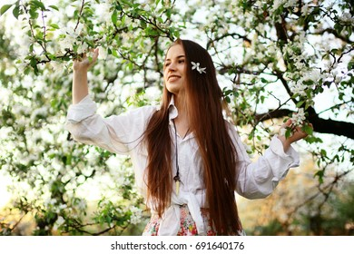 Spring portrait in apple blossoms young adult beautiful girl