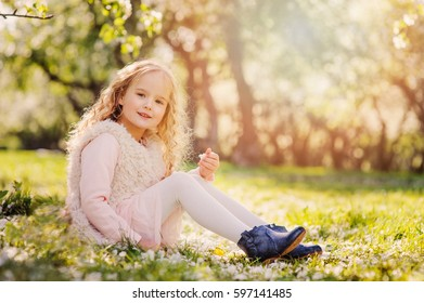 spring portrait of beautiful child girl with curly long hair walking outdoor in blooming garden