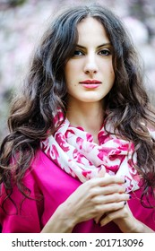 Spring portrait of a beautiful young woman in a pink blouse