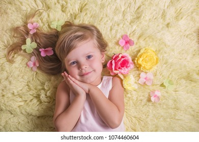 spring portrait of pretty smiling little girl on yellow background