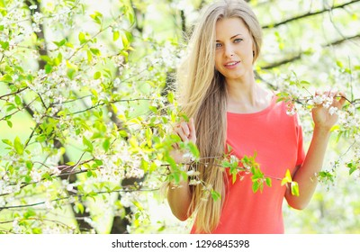 Spring portrait of pretty woman in a blooming garden