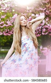 Spring portraits gorgeous young woman on  cherry blossom background