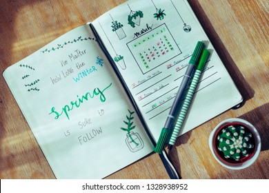 Spring quote. Lettering example in a journal on a wooden table. Diary notebook