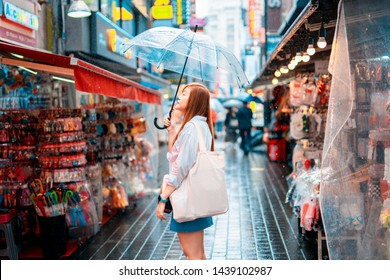 spring and raining season activity concept from beauty asian woman travel and shopping with hold her umbella with city and street food market background