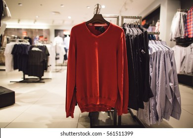 Spring red men's sweater in men's clothing store. Shopping concept.