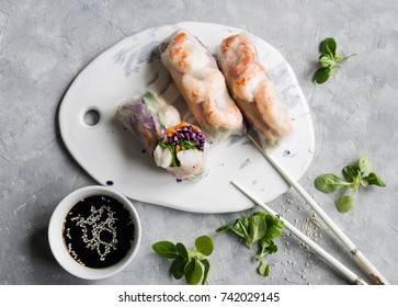Spring rolls with carrots, red cabbage, corn lettuce and shrimps on a white ceramic board. Soy sauce with sesame seeds on a gray background