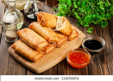 Spring rolls with chicken and vegetables on chopping board. Asian cuisine.