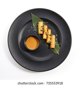 Spring rolls - fried Vietnamese rolls of rice edible paper on black matte plate next to cup with sauce. Pan-Asian menu of restaurant.