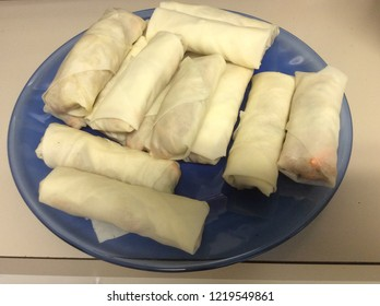 Spring rolls are ready to be fried. The stuffing inside compose of carrot, pork, egg, green veggies wrapped in sheet. This snack is famous Asian food. This picture has shadow in the left lower corner