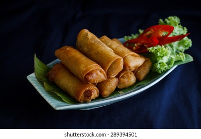 spring rolls with vegetable on blue cloth background, sill life image dark tone.