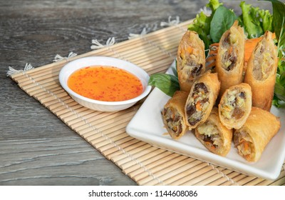 Spring rolls in white dish on brown wooden table Thai food
