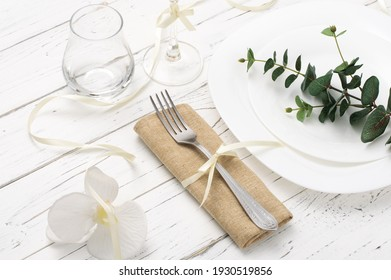 Spring romantic table setting with white flowers on white wooden table