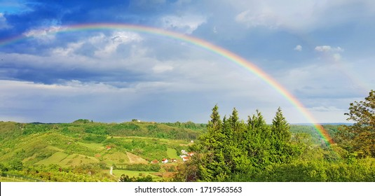 Spring rural rainbow landscape, view of green meadows and hills