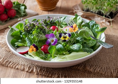 Spring salad with edible flowers - pansies, lamb's lettuce and fresh broccoli and kale microgreens