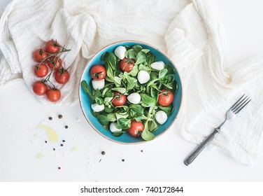 Spring salad with lamb's lettuce, mozarella and cherry-tomatoes in blue ceramic bowl over white backdrop, top view