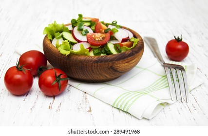 Spring salad with tomato, cucumbers and radish on a wooden background