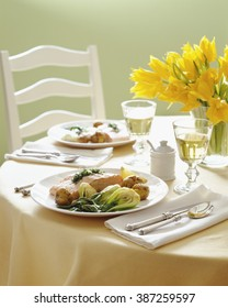 Spring salmon dinner table setting with white wine and flowers.