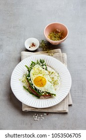 Spring sandwich of green aspargus, fried egg, feta cheese and micro greens on plate over light concrete background. Healthy eating, slimming, diet lifestyle concept. Flat lay, side view