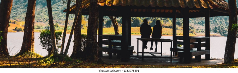 spring season activity concept from silhouette group of traveler or couple traveler stay in vintage cabin or summer house with cloth warm suit stand and see lake view in morning time