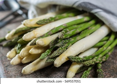 Spring season - fresh white and green asparagus on granit plank background