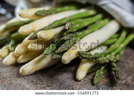 Spring season - fresh white and green asparagus on granite plank background