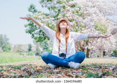 spring season with full bloom pink flower travel concept from beauty asian photographer woman enjoy with throw flower and see cherry blossom with soft focus background