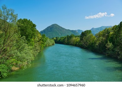 spring season on the river Toce with forest on the sides and mountains in the background and clouds in the sky