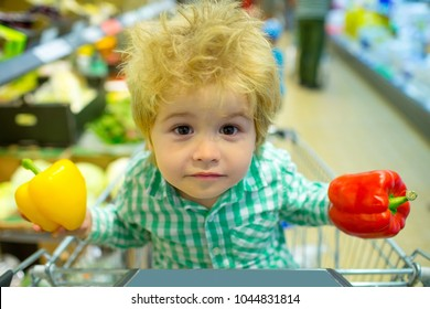 Spring shopping, vegetable purchase. Cute kid with a cool funny face in a store of vegetables and healthy food. A beautiful family, children face looks at the camera. Yellow and red pepper for dinner