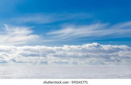 Spring sky over the snowy plain.