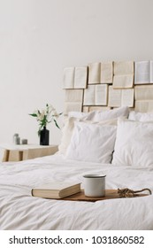 Spring still life. Breakfast in bed. White bedroom. Sweet home. Books, flowers and coffee cup. flat lay