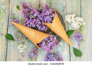 Spring still life with purple lilac flowers in waffle cones as ice cream on the background of old wooden table