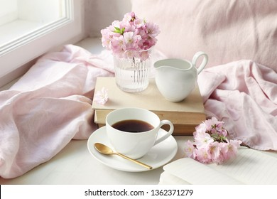 Spring still life scene. Cup of coffee, old books and milk pitcher. Vintage feminine styled photo. Floral composition with pink sakura, cherry tree blossoms on white table.