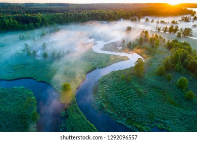 Spring stunning sunrise. Sun rising over green field with mist. Spring scenic nature.