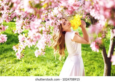 Spring Style. Beautiful Young Brunette Woman In Nice Spring Dress With A Bouquet Of Tulips.  Beautiful Spring Garden. Fashion Spring Summer Photo.