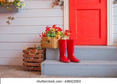 Spring summer autumn garden concept.  box with flowers. stage house. shoes is  standing on the threshold of the entrance. country house, cottage.red rubber boots outside
