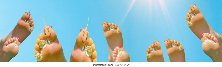 Spring summer background panorama banner long - Naked children's feet with smileys and blooming flowers isolated on blue sky with sun during the day - Shutterstock ID 1617345454