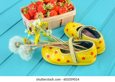 Spring or summer background with strawberries and tiny baby shoes