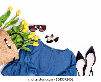 Spring summer basic denim casual city trend outfit set for woman: jeans blouse with wide sleaves, shoes, earrings, sunglasses and handbag full of yellow tulips.
