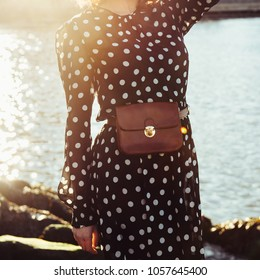 Spring summer casual female outfit with long black dress in polka dots with leather brow purse belt bag. Fashion trends concept.