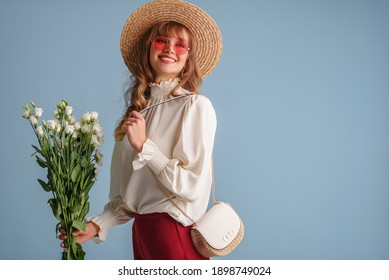 Spring, summer fashion conception: happy smiling woman wearing trendy outfit: pink sunglasses, white blouse, straw hat, with shoulder bag, posing on blue background. Copy, empty space for text