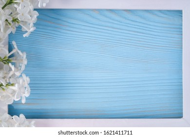 Spring or summer floral background for greeting card. White lilac and wooden frame on a blue background. Template for design with copy space.